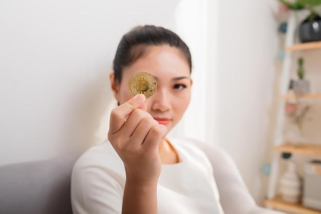 Mulher asiática ganha muito dinheiro! mulher atraente com bitcoin nas mãos e olha para a câmera.