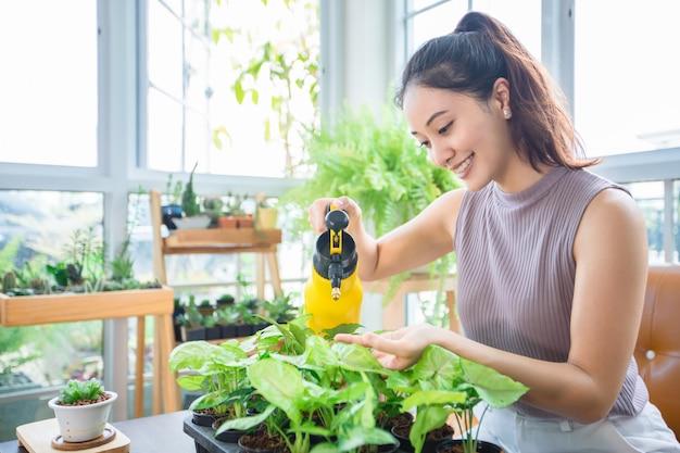 Mulher asiática gardener spraying water na planta no jardim para relaxar o dia em casa.