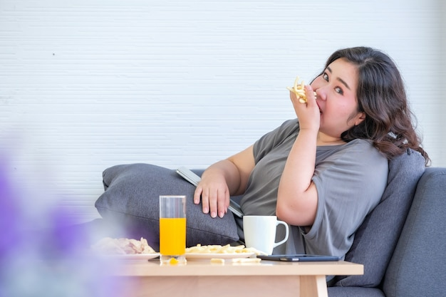 Mulher asiática gorda está gostando de comer batatas fritas