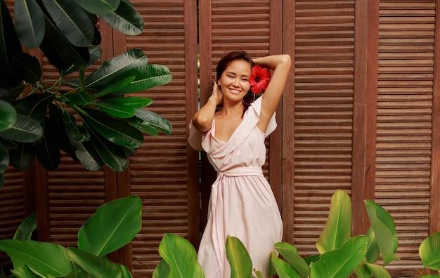 Mulher asiática graciosa com flor de hibisco nos cabelos posando sobre parede de madeira.