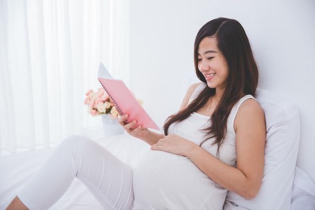 Mulher asiática grávida bonita que lê o livro de nota