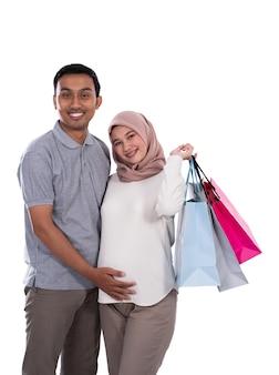 Mulher asiática grávida e marido carregando sacolas de compras