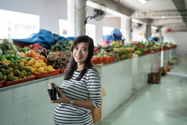 Mulher asiática grávida tirar dinheiro da carteira para pagar por mercadorias