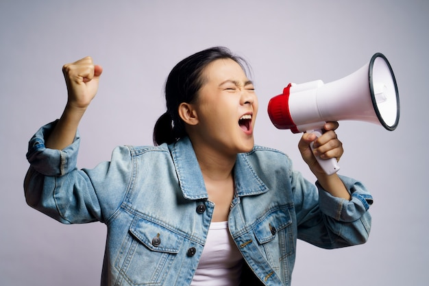 Mulher asiática gritando com megafone isolado.