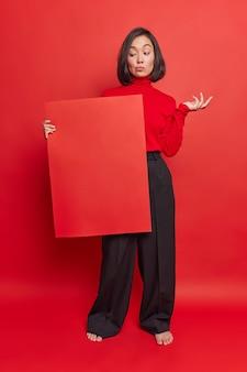 Mulher asiática hesitante olha com dúvida para o quadro de avisos encolhe os ombros sem saber que informações colocar usa calça de gola alta preta isolada sobre parede vermelha brilhante