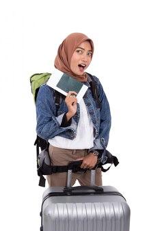 Mulher asiática hijab animado segurando o bilhete e o passaporte em pé perto da mala e carregando o saco
