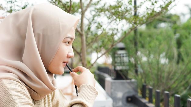 Mulher asiática hijab bebendo em um café