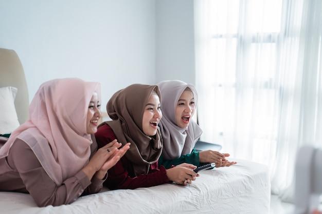 Mulher asiática hijab com amigos deitado na cama gosta de assistir televisão