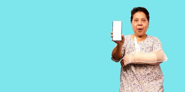 Mulher asiática idosa braço quebrado elenco apresentando telefone inteligente na parede azul