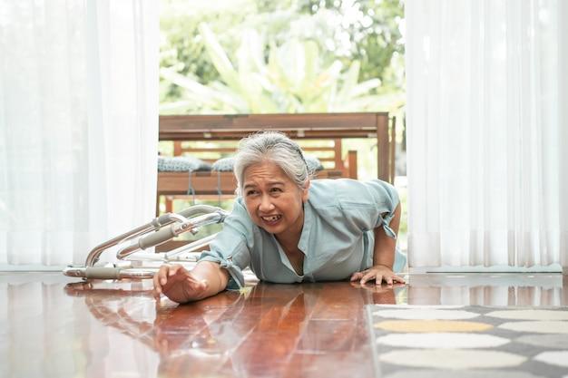 Mulher asiática idosa deitada no chão em casa