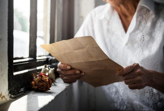 Mulher asiática idosa lendo uma carta