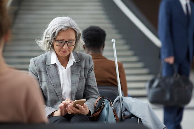 Mulher asiática idosa na área de espera