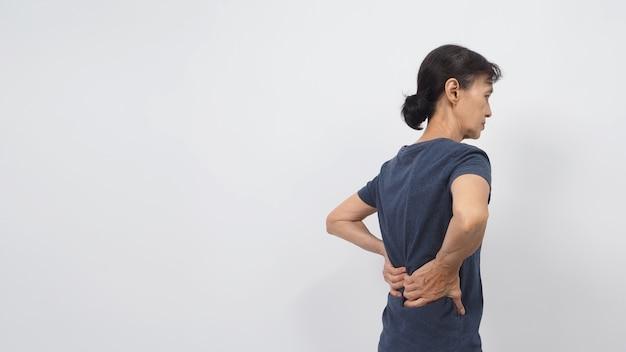 Mulher asiática idosa ou idosa apresentou postura de dor nas costas em fundo branco.