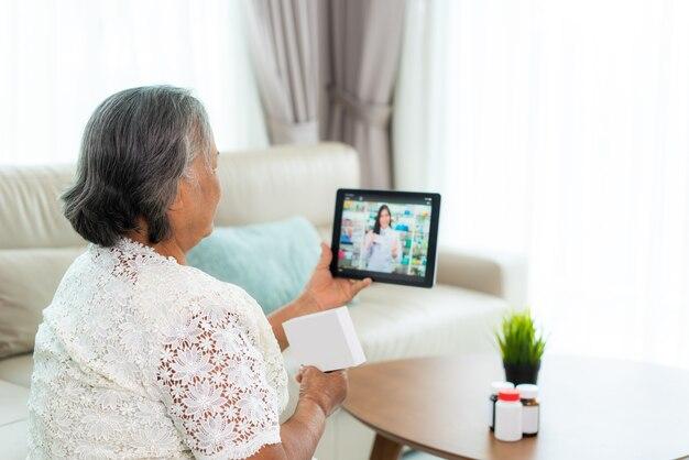 Mulher asiática idosa usando videoconferência, faça consulta online com a farmácia