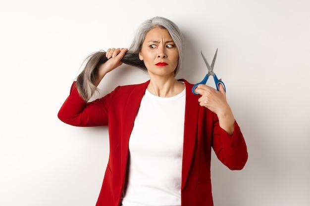 Mulher asiática indecisa segurando uma tesoura e parecendo em dúvida, pensando em cortar o cabelo, mudar o corte de cabelo, em pé sobre um fundo branco