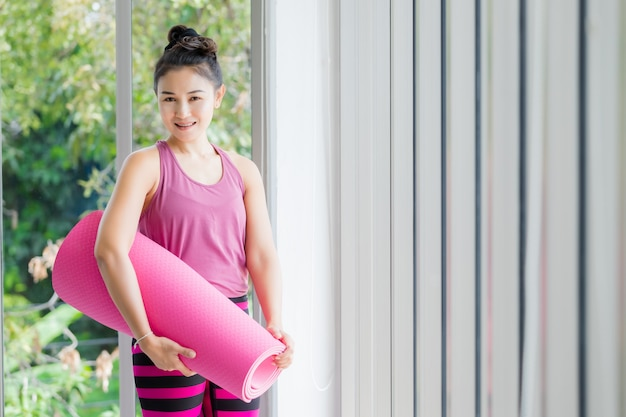 Mulher asiática, indo para a aula de yoga