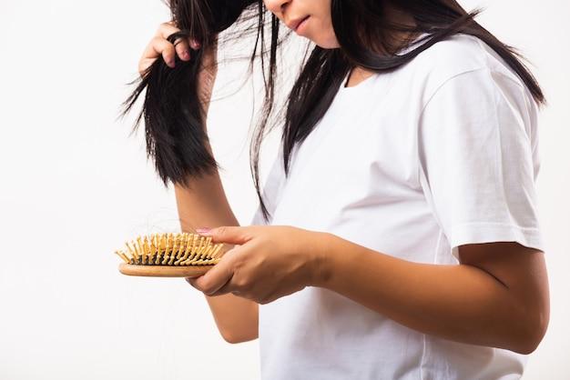Mulher asiática infeliz com cabelos fracos segurando a escova com cabelos longos e danificados