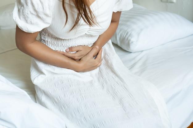 Mulher asiática infeliz sentada na cama e sofrendo de dor de estômago. conceito de problema de saúde