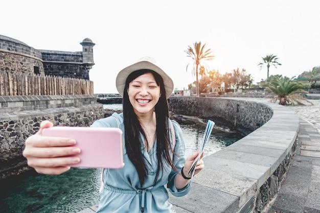 Mulher asiática influenciadora criando conteúdo com smartphone - menina chinesa se divertindo com a nova tecnologia de tendências - trabalho de atividade de geração milenar, conceito de juventude e tecnologia - foco no rosto