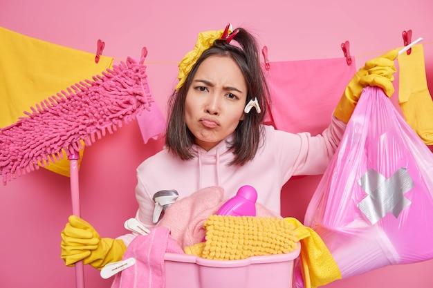 Mulher asiática insatisfeita com um sorriso afetado sente descontentamento e cansada de limpar segura o esfregão e o saco de polietileno cheio de lixo faz a casa