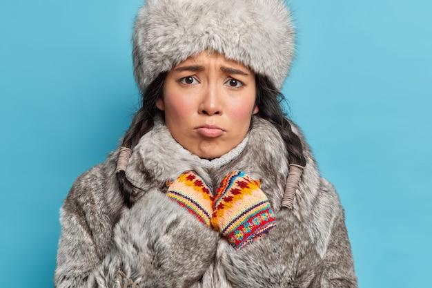 Mulher asiática insatisfeita mora no extremo norte vestida com agasalhos cinza, usa luvas quentes, franze a testa e treme de frio isolada sobre a parede azul