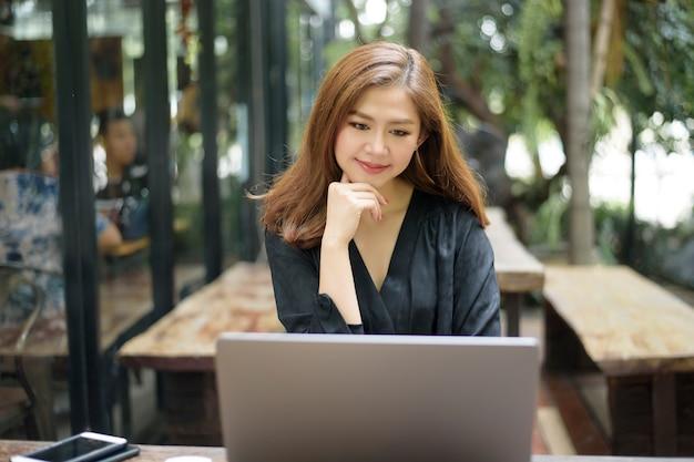 Mulher asiática inteligente está trabalhando com o computador portátil