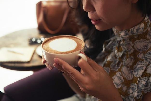 Mulher asiática irreconhecível, segurando a xícara de cappuccino no café