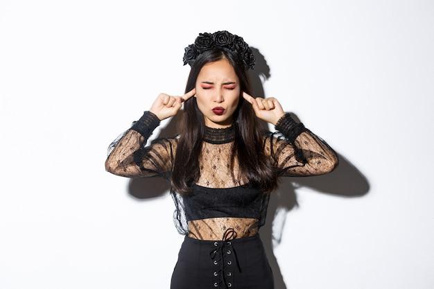 Mulher asiática irritada na fantasia de bruxa, fecha os olhos e os ouvidos com os dedos, sem vontade de ouvir, incomodada pelo barulho alto, em pé em um vestido gótico e uma grinalda sobre fundo branco.