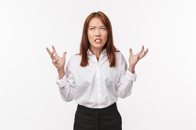 Mulher asiática irritada odeia clientes irritantes. mulher irritada, angustiada e tensa, de camisa branca, aperta as mãos nos punhos, perdendo a paciência, olhando para cima, fervendo de aborrecimento,