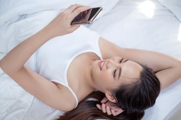 Mulher asiática joga telefone em casa ela estava dormindo e relaxada.