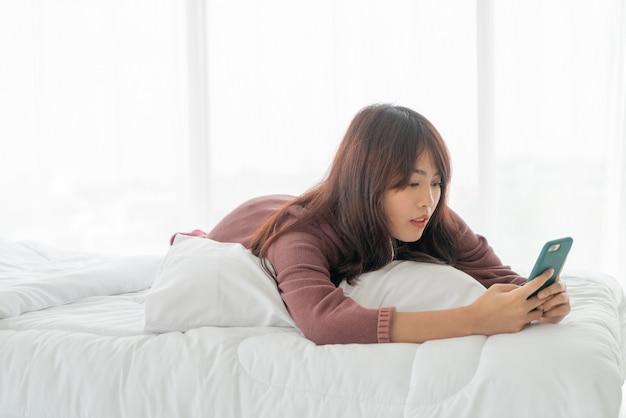 Mulher asiática jogando smartphone na cama