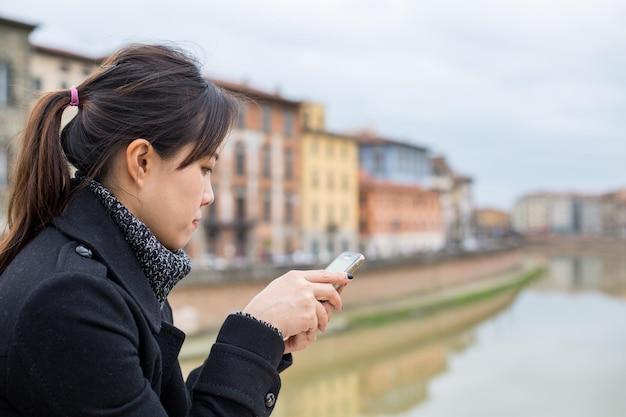 Mulher asiática jogar smartphone em vista para o rio pisa itália.