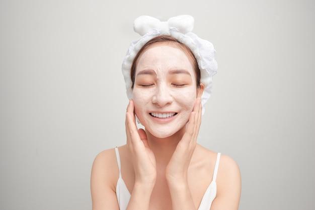 Mulher asiática jovem alegre com máscara de argila facial isolada no fundo branco.
