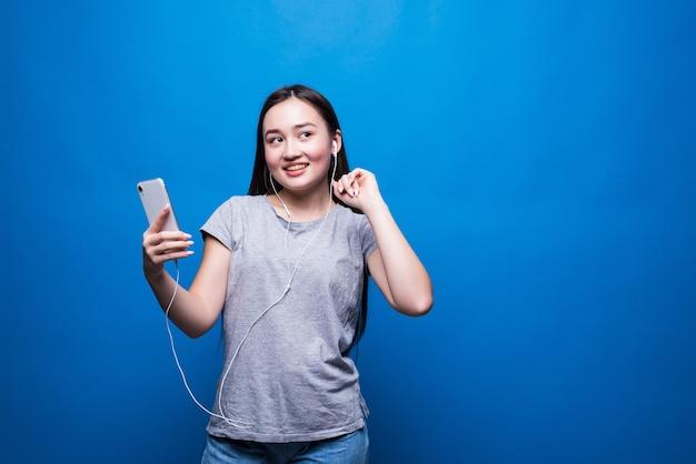 Mulher asiática jovem alegre usando fones de ouvido, ouvindo música e dançando, isolada sobre a parede azul