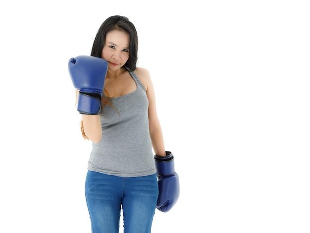 Mulher asiática jovem ativa positiva em roupa casual e luvas de boxe azuis socando a câmera enquanto pratica estilo de vida saudável contra um fundo branco