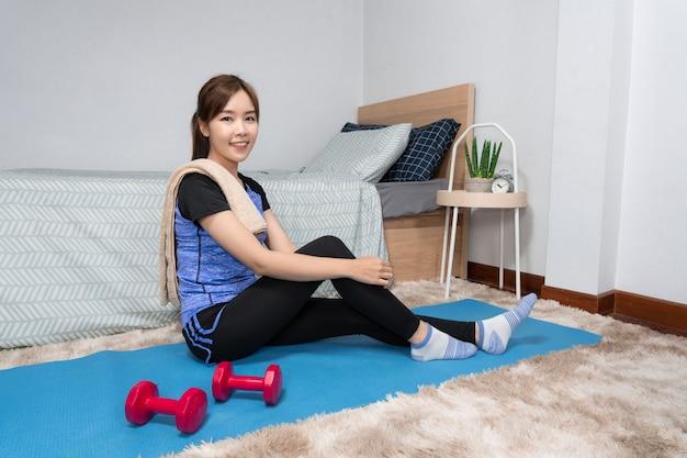 Mulher asiática jovem atraente e saudável fazendo exercícios em casa durante o treino