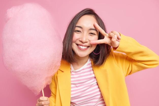 Mulher asiática jovem bonita sorri positivamente faz gesto de vitória sobre o olho tem humor otimista contém algodão doce delicioso usa jaqueta amarela tem poses de dente doce contra a parede rosa.