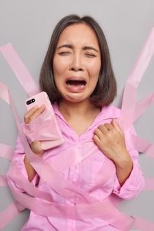 Mulher asiática jovem deprimida chora com expressão triste segurando celular moderno, não podendo usar gadget embrulhado em gesso preso em cativeiro