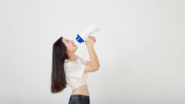 Mulher asiática jovem e alegre segurando o anúncio de um megafone em um estúdio isolado