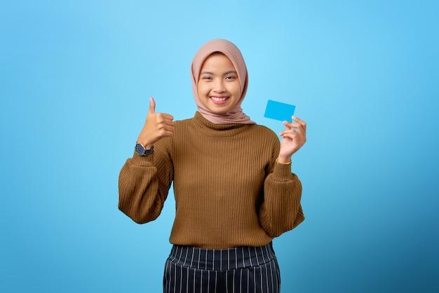 Mulher asiática jovem e alegre segurando um cartão de crédito e mostrando um gesto de polegar para cima sobre fundo azul