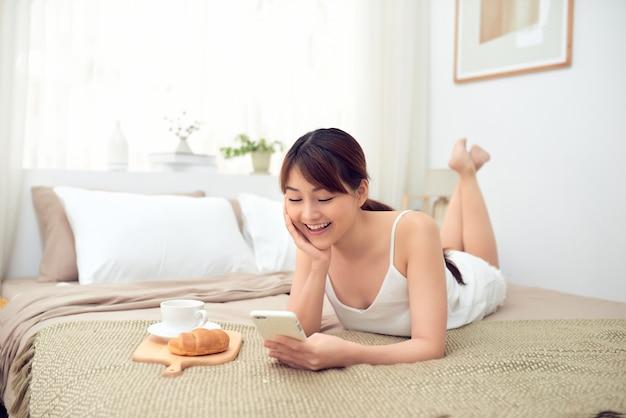 Mulher asiática jovem e alegre usando o celular, deitada na cama de manhã