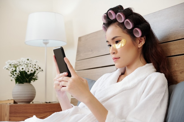 Mulher asiática jovem e atraente com rolos de cabelo e tapa-olhos, sentada na cama e enviando mensagens de texto para um amigo ou usando um aplicativo móvel