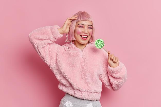 Mulher asiática jovem e atraente elegante com penteado rosa segurando deliciosos doces verdes vestidos com um casaco da moda