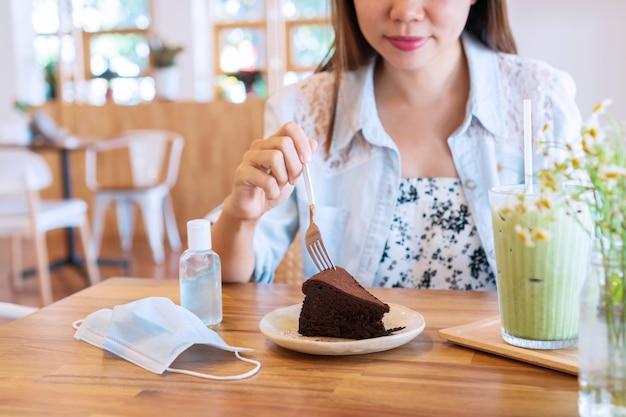 Mulher asiática jovem e bonita comendo bolo de chocolate com leite com leite matcha gelado, gel desinfetante e máscara cirúrgica na mesa de madeira de um café