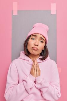 Mulher asiática jovem e bonita implora por favor, pede ajuda ou pede favores sobre algo suplicante, usa um moletom casual e um chapéu tem uma expressão carrancuda em poses internas