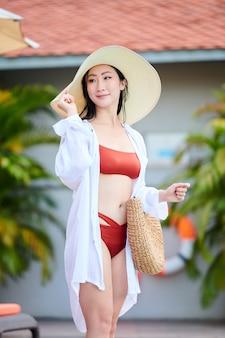 Mulher asiática jovem e bonita sorridente em um vestido de camisa segurando a ponta do chapéu de palha em pé na praia