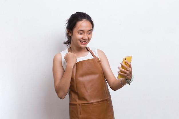 Mulher asiática jovem e feliz, bartender ou garçonete usando smartphone móvel em fundo branco