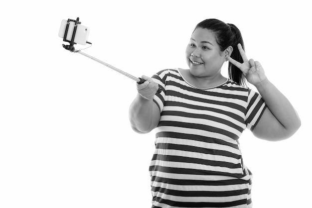 Mulher asiática jovem e feliz com excesso de peso dando o sinal da paz enquanto tira uma foto de selfie com o celular no stick de selfie