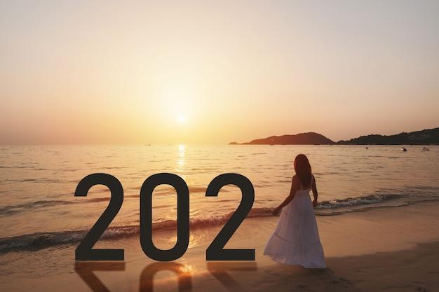 Mulher asiática jovem e solitária em pé na praia ao pôr do sol com o conceito de ano novo 2021