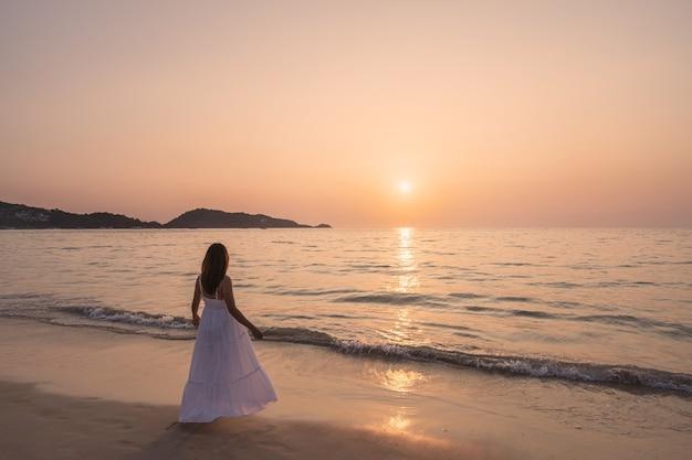 Mulher asiática jovem e solitária em pé na praia ao pôr do sol